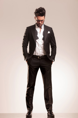 見下ろしながら彼のポケットで両方の手で立っている若いエレガントなビジネス人。