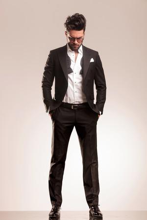 Jonge elegant zaken man die met beide handen in zijn zak, terwijl naar beneden te kijken.