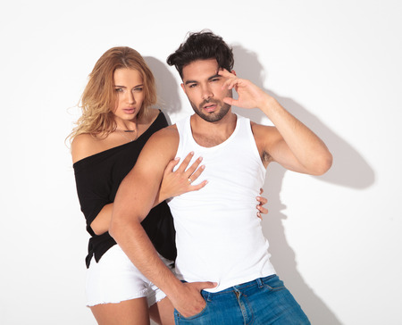 man behind: Casual young couple posing together on white studio background.