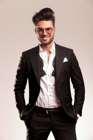 undone: Happy elegant business man smiling at the camera while holding both hands in his pocket. Stock Photo