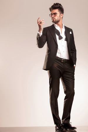 male body: Full body picture of a elegant business man standing on grey studio background, holding one hand in his pocket and the other one up.