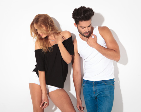 Fashion man and woman posing on white studio background while looking down.