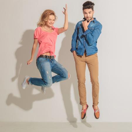 mujeres fashion: Mujer joven que salta junto a su amante mientras que él está sosteniendo su mano a la barbilla. Foto de archivo