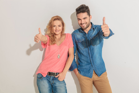 jean: Happy young couple leaning on a wall while showing the thumbs up gesture. Stock Photo