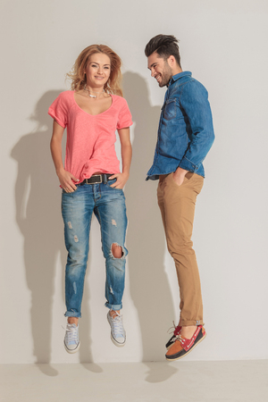 fashion boy: Casual young couple jumping together while smiling.