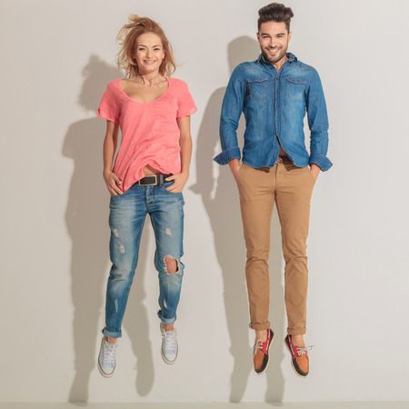 standing together: Young casual couple jumping while holding theri hands in pockets.