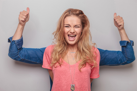 funny people: Young blonde woman screaming while her lover is standing behind her showing the thumbs up gesture with both hands.