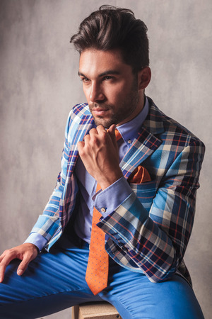 hand on the chin: Pensive young business man sitting while holding his hand to the chin.