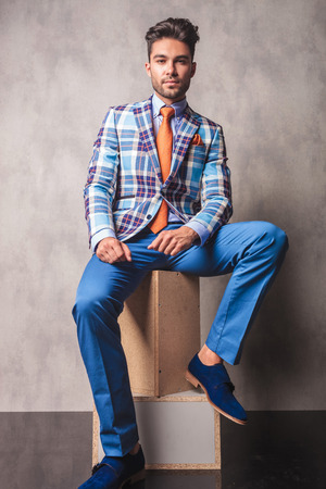 Full body picture of a fashion business man sitting on wood boxes, on studio background. Archivio Fotografico