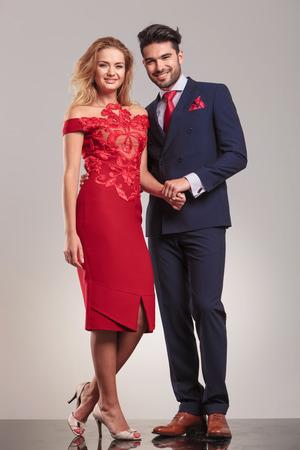 uomo rosso: Felice coppia elegante mano nella mano mentre in piedi sullo sfondo di studio. Archivio Fotografico