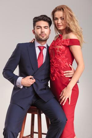 hombre sentado: Hombre elegante y guapo cerrar su chaqueta mientras sostiene a su esposa. Foto de archivo