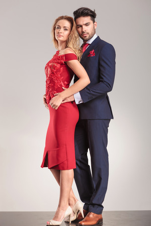 dress suit: Full body picture of a young elegant couple standing on studio background. Stock Photo