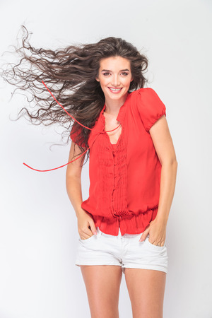 pocket: Happy young woman holding her hands in pockets while her hair is blowing.