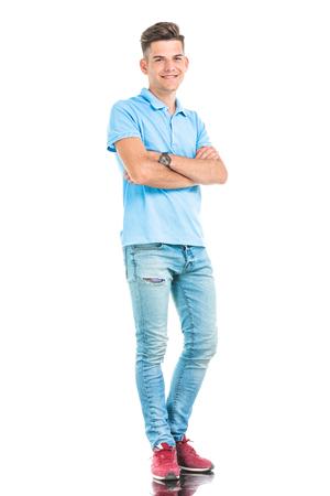 mani incrociate: quadro completo del corpo di un giovane uomo casual in piedi con le mani incrociate.