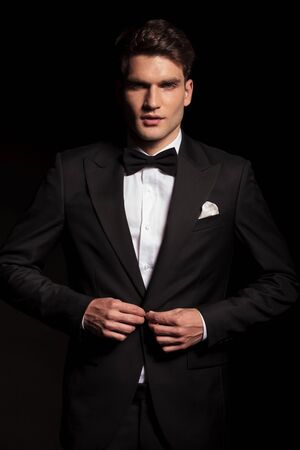 unbutton: Picture of a young elegant man closing his jacket.