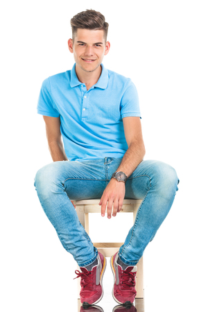 椅子に座って若いカジュアルな男の全身画像です。