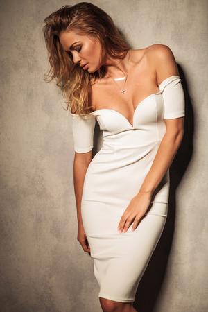 poses de modelos: mujer elegante mirando hacia abajo mientras que presenta cerca de una pared gris.