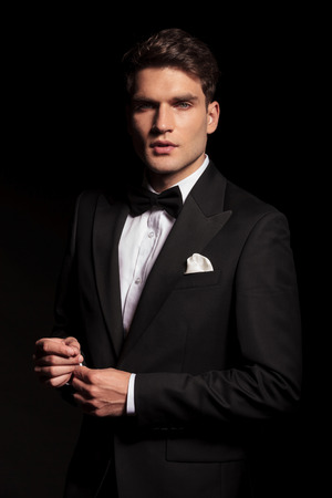 traje: Vista lateral de un hombre joven elegante que se fija la manga mientras mira a la cámara. Foto de archivo