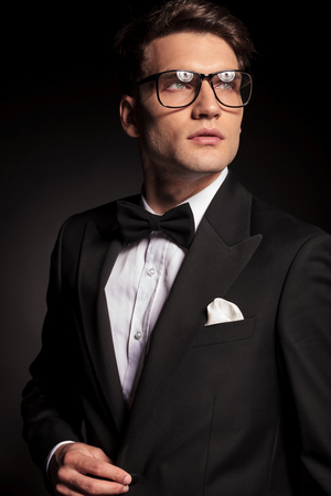 glasses model: Portrait of a young handsome man looking up while closing his jacket. Stock Photo