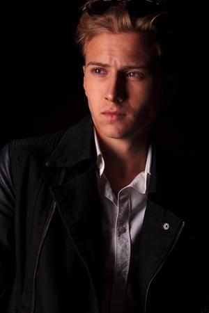 viso uomo: Primo piano immagine di un bel giovane di moda in cerca di distanza dalla fotocamera.