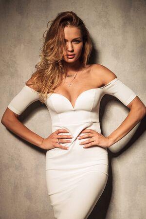 mujer elegante: Mujer elegante atractiva que mira a la cámara mientras mantiene las manos en la cintura.