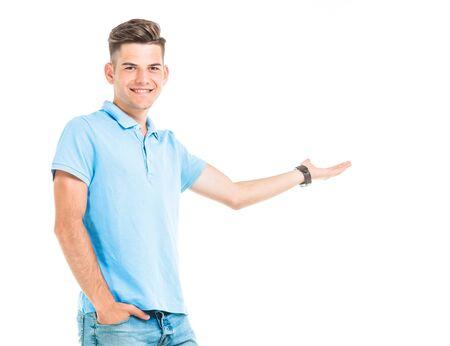 beau mec: Attractive jeune homme tenant sa main dans la poche tout en présentant quelque chose.