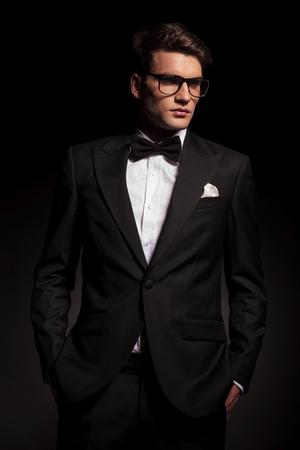 modelos hombres: Hombre joven elegante que mira lejos de la cámara mientras mantiene las manos en los bolsillos.