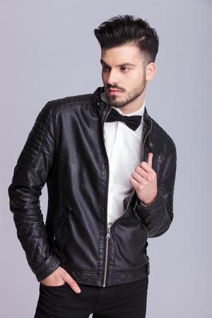 上着を引きながら彼のポケットに 1 つの手を保持しているハンサムな若いビジネス人の映像。 写真素材