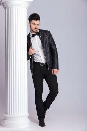 body image: Full body image of a handsome business man pulling his leather jacket while leaning on a white column. Stock Photo