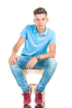 hombre sentado: Hombre joven pensativo sentado en una silla, en el fondo aislado. Foto de archivo