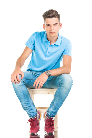 Pensive young man sitting on a chair, on isolated background. Stock Photo