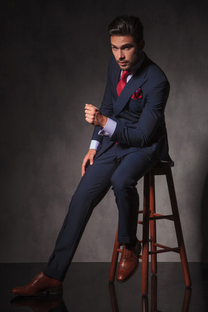 Side view of a young elegant business man sitting on a chair, on studio background.