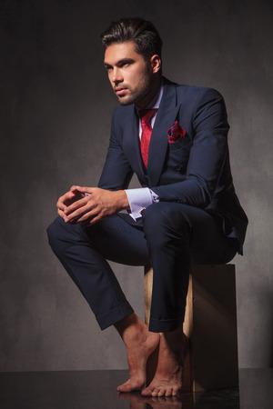pies masculinos: Pensativo hombre de negocios joven sentado con las manos mientras se mira lejos. Foto de archivo