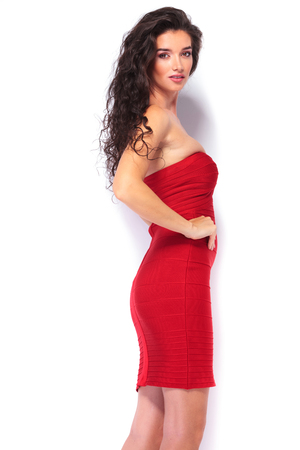 attractive  female: Side view of a gorgeous young woman wearing a sexy red dress, looking at the camera. Stock Photo
