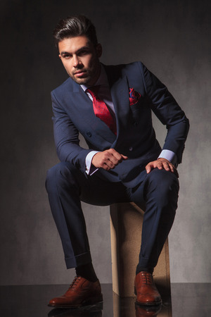 elegant business man: Full body picture of a young elegant business man sitting on a wood box while thinking.