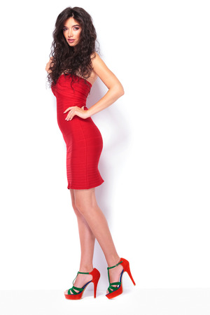 Full length picture of a hot young lady standing on white studio background.