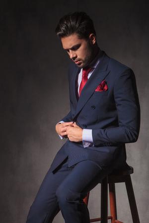 cerrando negocio: Young business man looking down while closing his jacket.