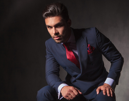 Young handsome business man looking at the camera while sitting on studio background.