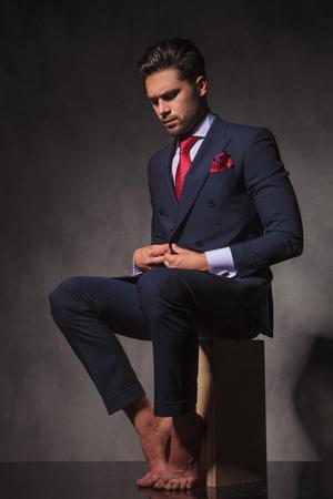 Descalzo joven hombre de negocios de cerrar su chaqueta mientras está sentado en una caja de madera.