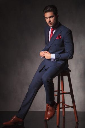 hombre sentado: Todo el cuerpo de un hombre de negocios joven hermoso que mira a la c�mara mientras el cierre de su chaqueta. Foto de archivo