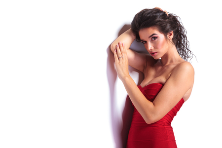 fashion dress: Sexy young woman holding her hair up while leaning on a wall. Stock Photo