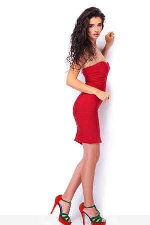 mujer cuerpo completo: Foto de cuerpo entero de una hermosa joven de pie en el fondo blanco del estudio. Foto de archivo