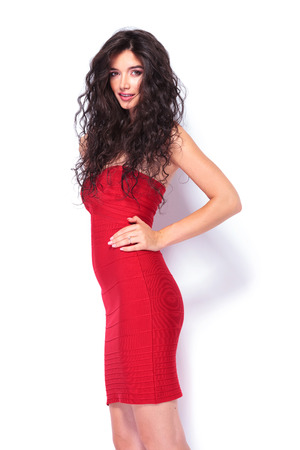 red dress: Picture of a sexy elegant woman holding her hand on her waist while smiling at the camera. Stock Photo