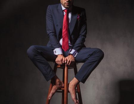 pies masculinos: Cuerpo de un hombre de negocios sentado en una silla, sobre fondo gris studio. Foto de archivo