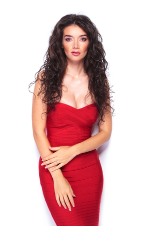 provocative: Provocative young lady posing on studio background wearing a sexy red dress. Stock Photo