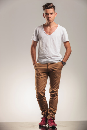 hansome: hansome young fashion men standing on studio backgroung with his hands in pockets Stock Photo