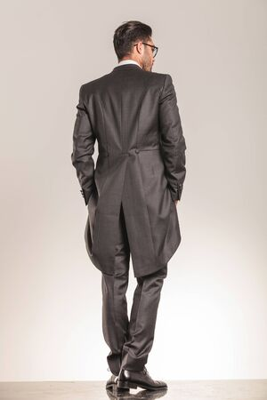 Back view of a elegant business man walking with his hands in pockets on studio background.