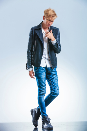 messy hairstyle: skinny young boy posing while looking down and holding his hand on the leather jacket