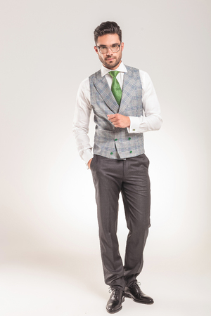 vest: Full length picture of a elegant business man standing with one hand in his pocket.