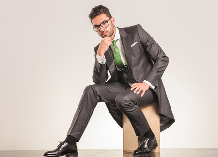 young businessman: Elegant business man sitting on a wood box while holding his hand to the chin thinking.